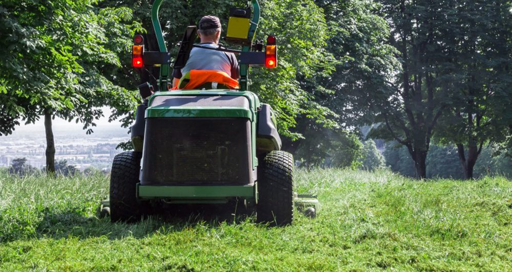 male-using-lawn-mower-and-cutting-grass-around-him-a-green-landscape_t20_EnX9WY